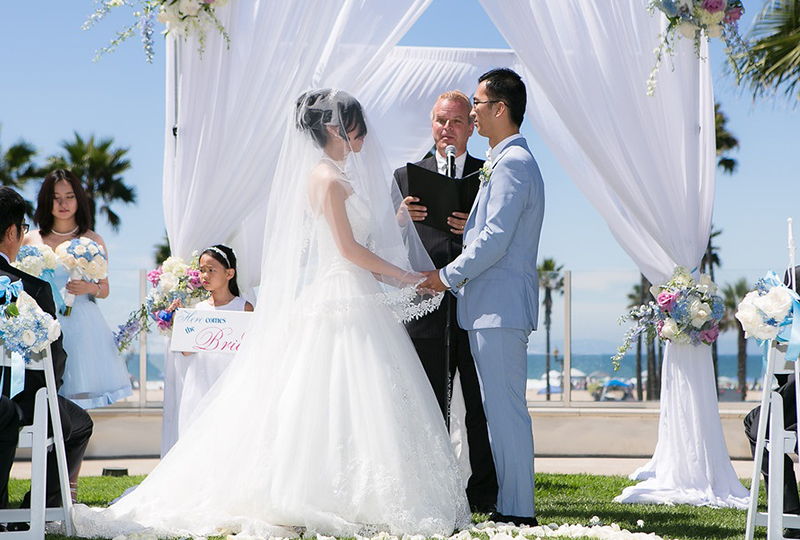 Couple saying I DO at their wedding ceremony filled with beautiful wedding decorations in Orange County http://RoyceWeddings.com Call: 626-560-2537